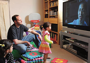 Phoebe, Hugh and Rory Dainer watch the DVD Rupa made them before deploying to Afghanistan.