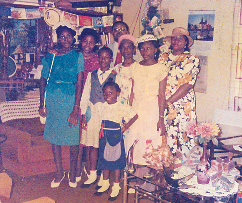 Crannough Jones (second row, far left) stands in front of her sister, Carmen, in a photo taken with other relatives on Christmas 1985 at their home in Liberia. Their mother, Patricia Jones, wearing a flowered dress and hat, is on the right. Courtesy photo