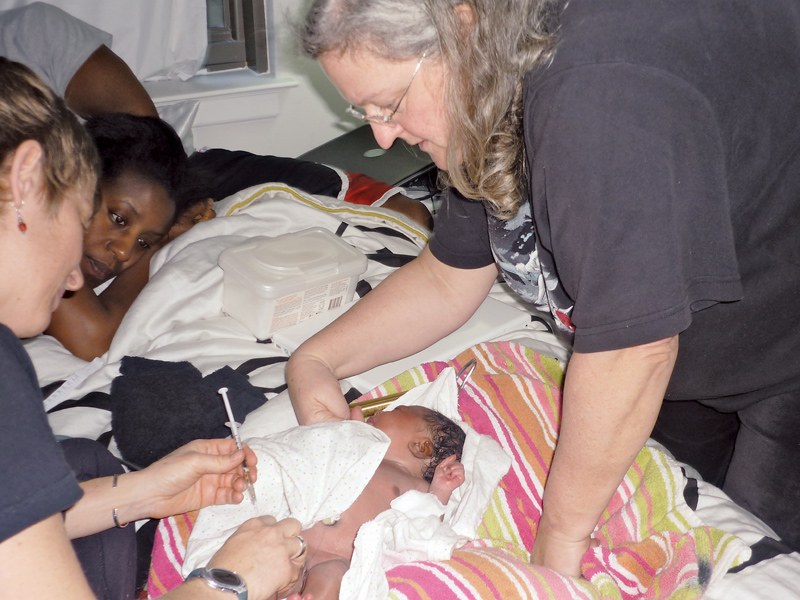 Dana Evans gazes at her new baby, Ever, as certified nurse-midwife Mairi Rothman checks out the newborn in March 2011. Photo courtesy of Dana Evans