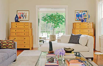 The neutral living room furnishings provide a backdrop for colorful art and sculpture.
